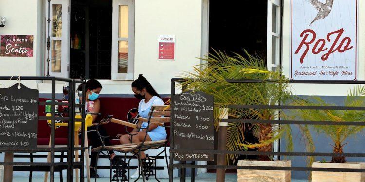 Dos mujeres esperan fuera del Bar Rojo, el 25 de agosto de 2021, en La Habana, Cuba.    Ernesto Mastrascusa, EFE.