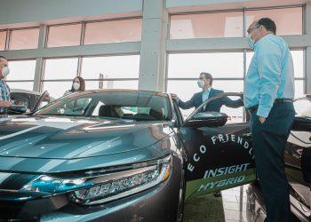 El presidente ejecutivo del Banco Popular Dominicano, Christopher Paniagua, se apresta a montarse en un vehículo ECO. Le acompañan la Maribel Bellapart y, en primer plano, de izquierda a derecha, Víctor Carvajal y Wilfredo Lithgow.