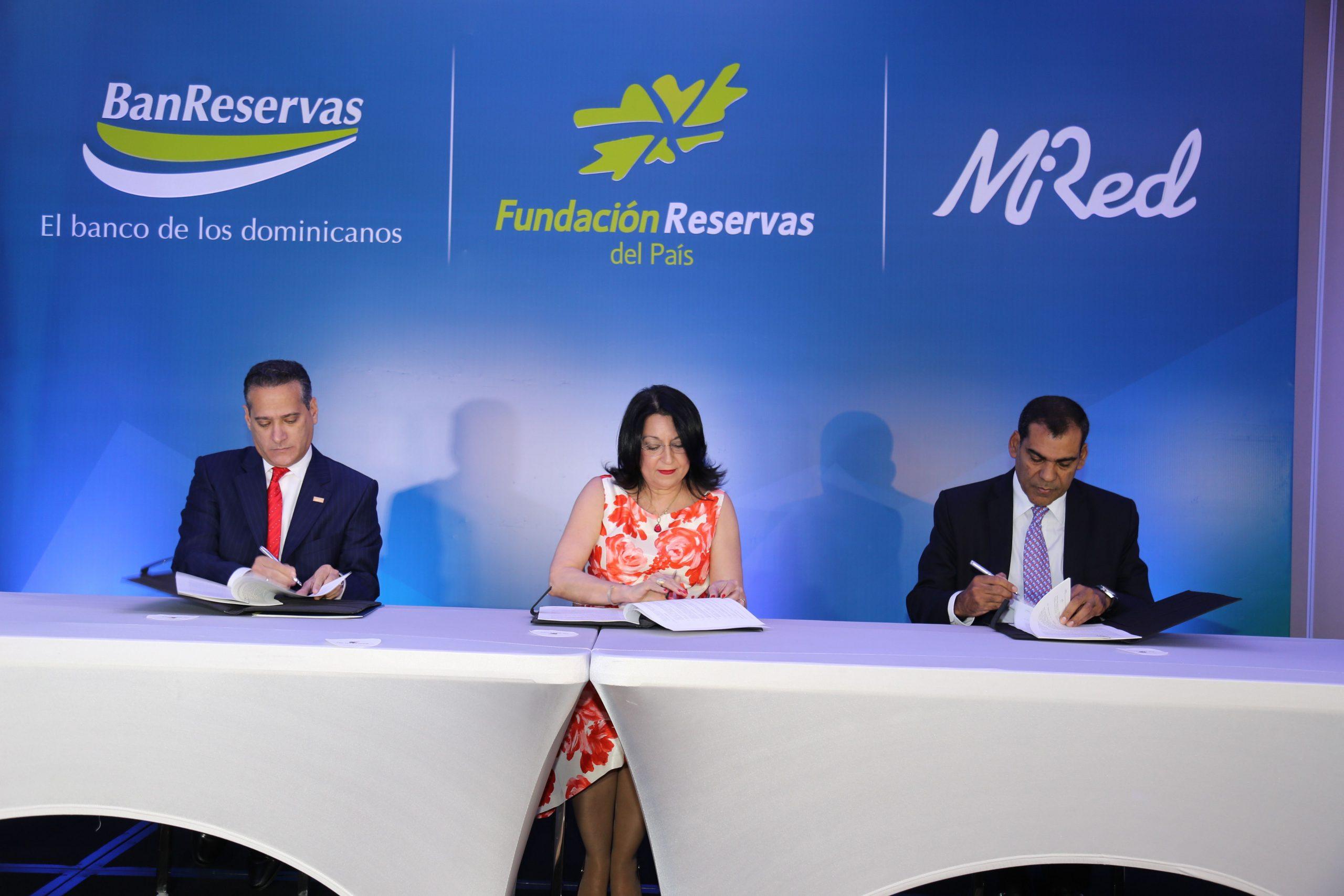 Rienzi Pared Pérez, de BanReservas; Rosa Rita Álvarez, de al Fundación Reservas del País, y Luis Bencosme, de Mi Red, firman el acuerdo.
