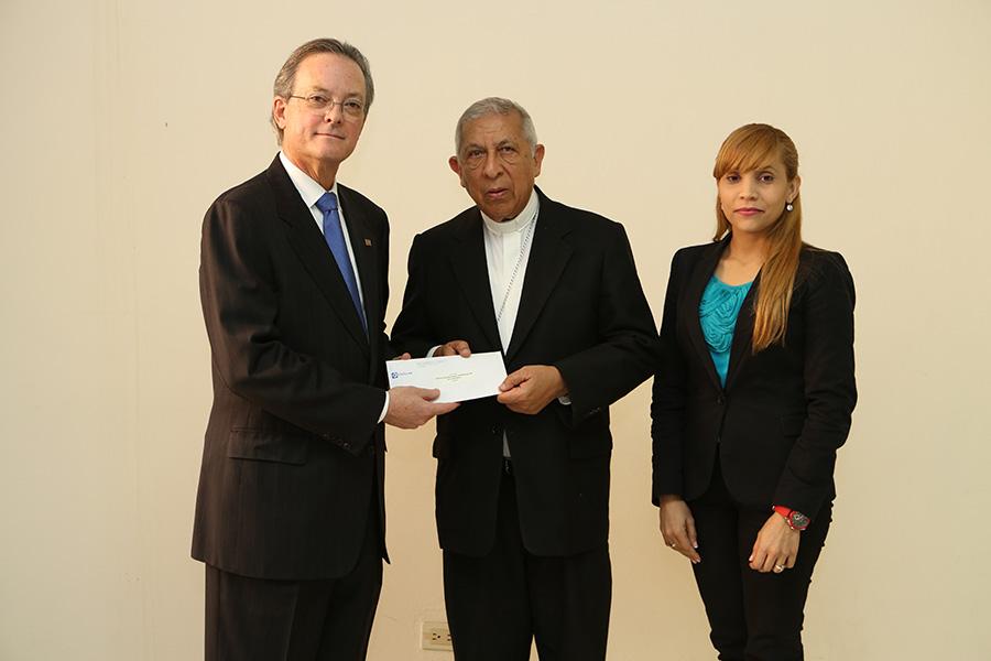 El presidente del Banco Popular, Manuel A. Grullón, entrega el aporte social al arzobispo Ramón Benito de la Rosa y Carpio. Les acompaña la señora Walkiria Estévez, directora ejecutiva de Cáritas Arquidiocesana de Santiago.