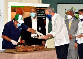 El presidente Luis Abinader comparte con los posicultures en una degustacion de cerdo. (1)