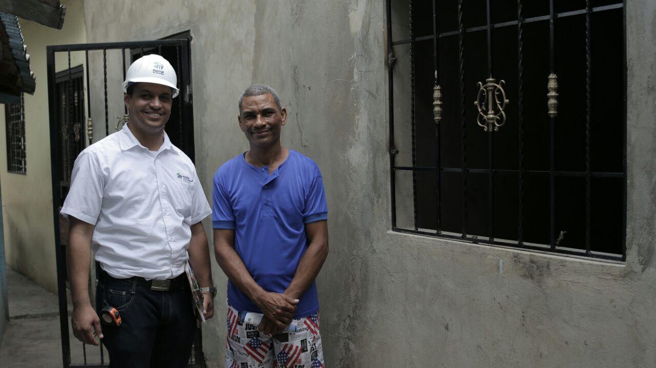 foto 1. un ingeniero de hábitat junto a un beneficiado y su mejora habitacional