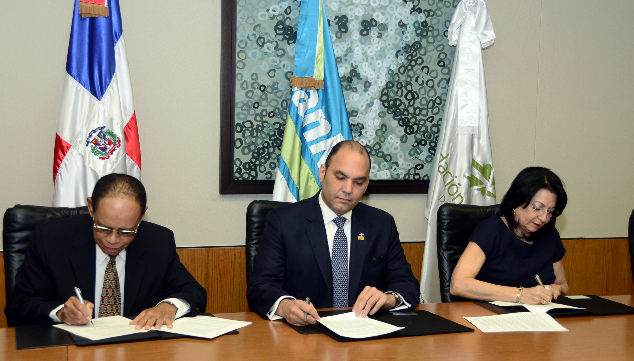 Lidio Cadet, Enrique Ramírez Paniagua y Rosa Rita Álvarez durante la firma del acuerdo en la Torre BanReservas.