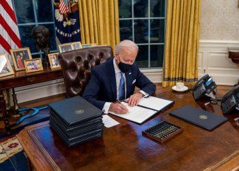 El presidente de EEUU, Joe Biden, firma un documento desde el Despacho Oval de la Casa Blanca.