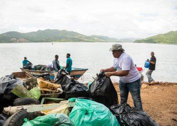Trabajadores de la minera recogen desperdicios en las riberas de la presa de Hatillo.