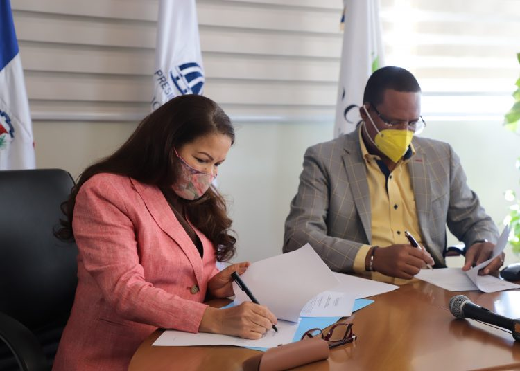 La directora de la ADESS, Digna Reynoso, y el titular de Pro Consumidor, Eddy Alcántara, en el momento que firman el acuerdo.
