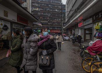 Personas caminan por las calles portando su mascarilla en Wuhan, China. | Roman Pilipey, EFE.