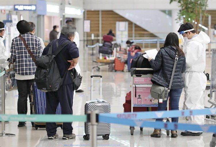 Personal del aeropuerto internacional de Incheon, al este de Seúl, comprueban que los pasajeros que llegan, lo hacen con una PCR negativa.  |Yonhan vía EFE.