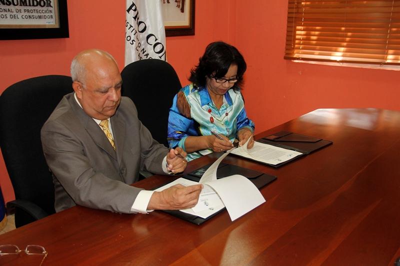 Oquendo Medina y Altagracia Paulino durante la firma del acuerdo.
